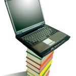 stack of books with laptop